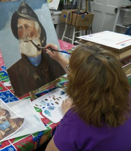 Cathy reworks an old painting she recently acquired.