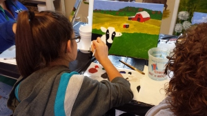 Our youngest painter working on her cow