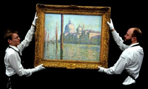 Sotheby's staff prepare to hang Claude Monet's Le Grand Canal, which sold for £23.7m. Photograph: John Stillwell/PA
